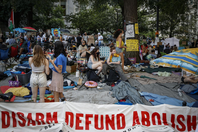 Protesters rest on a grassy area surrounded by signs calling for the changes and abolition of police forces at an encampment outside City Hall, Friday, June 26, 2020, in New York. (AP Photo/John Minchillo)