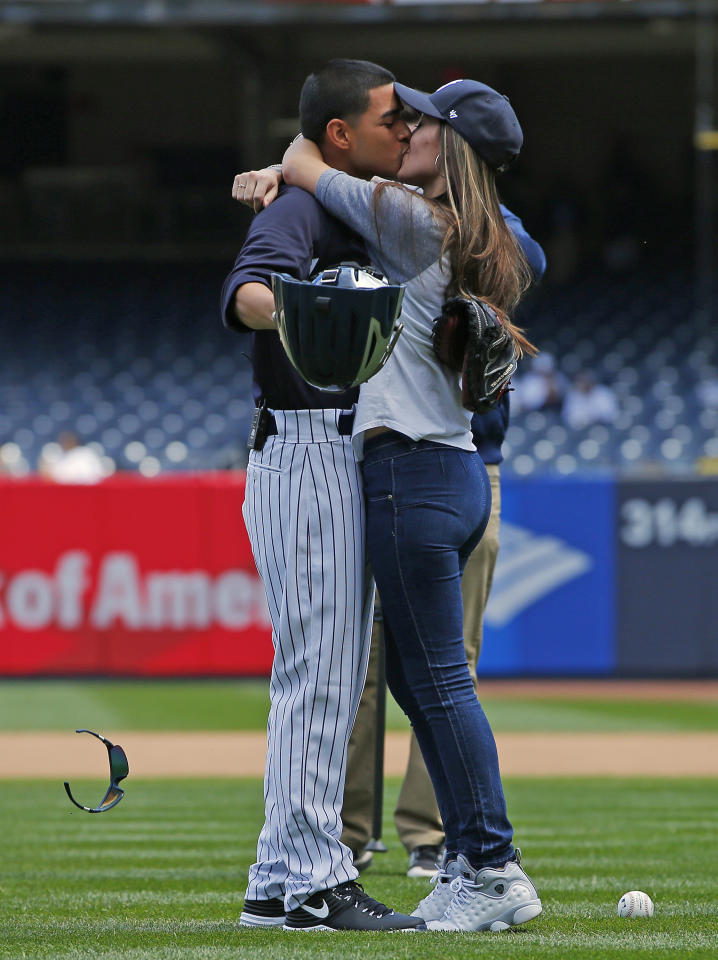 <p>U.S. Army Specialist Daniel Paredes kisses his wife Selena after surprising her on his return from Iraq. Selena threw out the first pitch before game one of a doubleheader between the Houston Astros and New York Yankees at Yankee Stadium on May 14, 2017 in New York City. (Photo by Rich Schultz/Getty Images) </p>