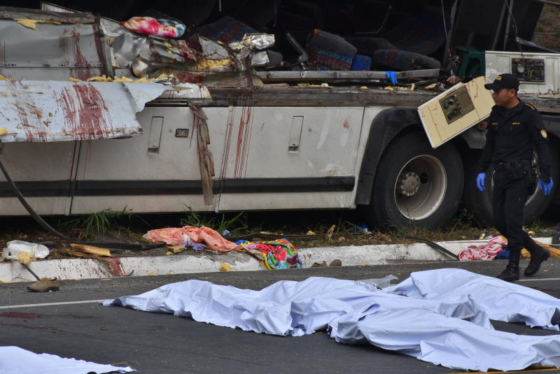 A police officer walks past the covered bodies of passengers that perished when a bus crashed with a trailer truck in Gualan, Guatemala, Saturday, Dec. 21, 2019. The accident killed at least 21 people and left a dozen wounded, according to the national disaster agency. (AP Photo/Carlos Cruz)