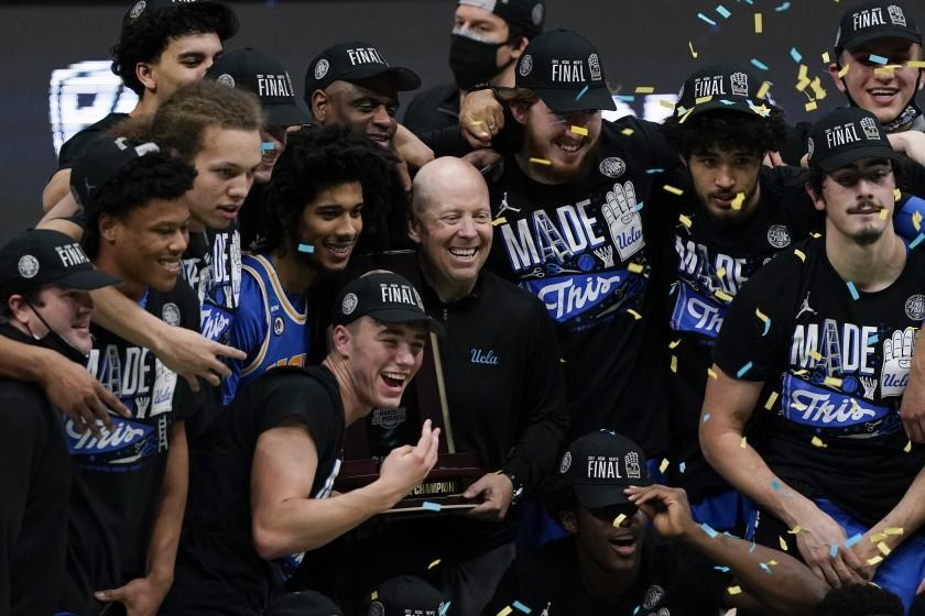 UCLA head coach Mick Cronin, center, celebrates with his team after an Elite 8 game against Michigan.