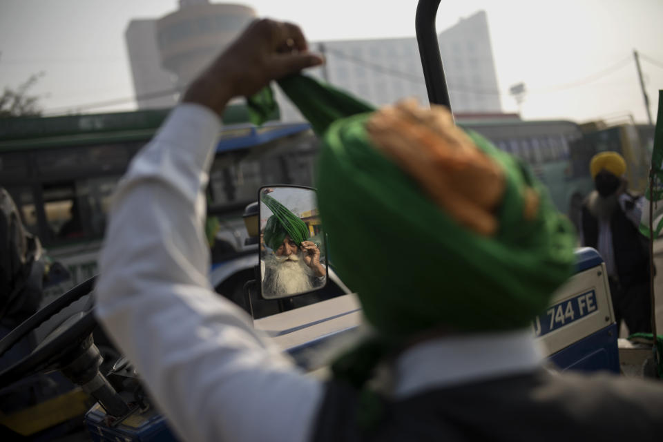 "Jagir Singh, 71, looks into the mirror of a tractor as he ties his turban before joining fellow protesters protesting against new farm laws at the Delhi-Haryana state border, India, Tuesday, Dec. 1, 2020. Instead of cars, the normally busy highway on the outskirts of New Delhi that connects most northern Indian towns to the capital is filled with tens of thousands of protesting farmers, many wearing colorful turbans. It's a siege of sorts and the mood among the protesting farmers is boisterous. Their rallying call is ""Inquilab Zindabad"" (""Long live the revolution""). (AP Photo/Altaf Qadri)"