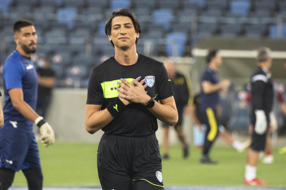Referee Sapir Berman attends a warm-up before an Israeli Premier League soccer match between Hapoel Haifa and Beitar Jerusalem in the northern Israeli city of Haifa, Monday, May 3, 2021. Israeli soccer's first transgender soccer referee took the field Monday for the first time since coming out publicly as a woman last week. (AP Photo/Sebastian Scheiner)