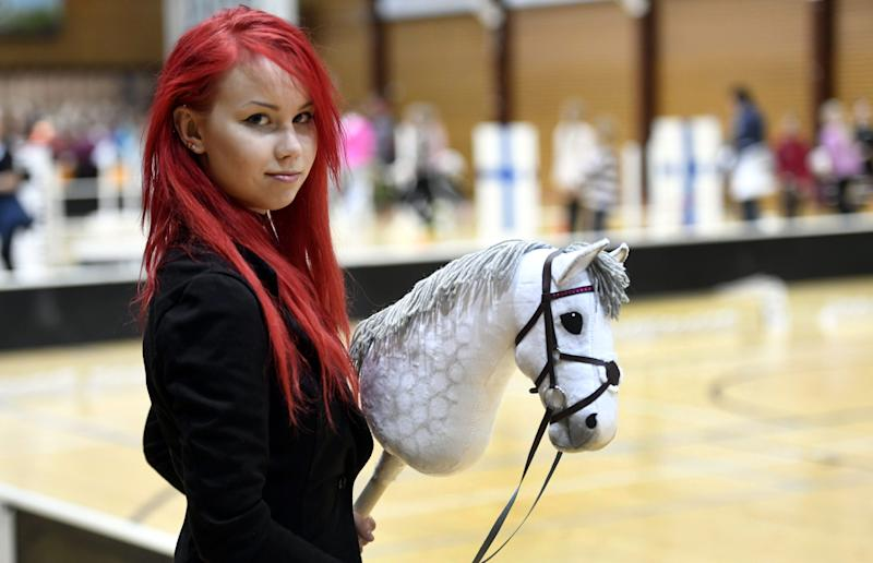 Sporting dyed red hair 20-year old Alisa Aarniomaki holds her hobby-horse, during the hobby-horsing Finnish championships in Vantaa, Finland, Saturday, April 29, 2017.  Thousands of young people in Finland have taken up hobby-horsing, with its strong therapeutic element and a social media subculture, it is physically demanding with gymnastic moves for the dressage and show jumping disciplines. (Heikki Saukkomaa/ Lehtikuva via AP)