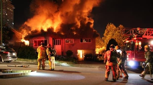 Firefighters are pictured at the scene of a house fire in Burnaby at 9930 Lyndhurst Street early Sunday.  (Ryan Stelting - image credit)