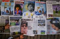 A worker arranges the front pages of Spanish newspapers paying tribute to late soccer legend Diego Maradona at Las Ramblas, in Barcelona