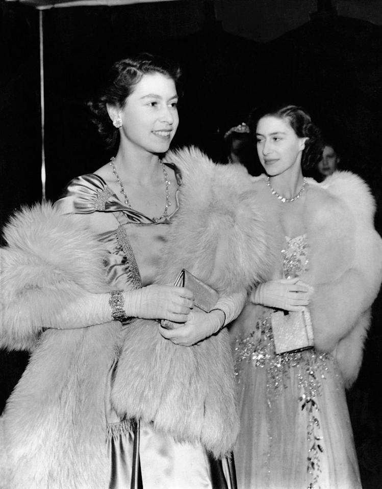 <p>Then-Princess Elizabeth and Princess Margaret went glamorous for a royal variety performance in London. The sisters each wore an elaborate ball gown with fur wraps.</p>