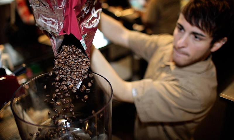 An employee pours coffee beans into a grinder at a Costa Coffee shop in London