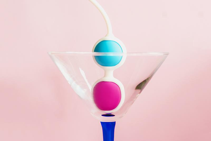Color Kegel balls in a triangle cocktail glass on pink background. Concept of women health