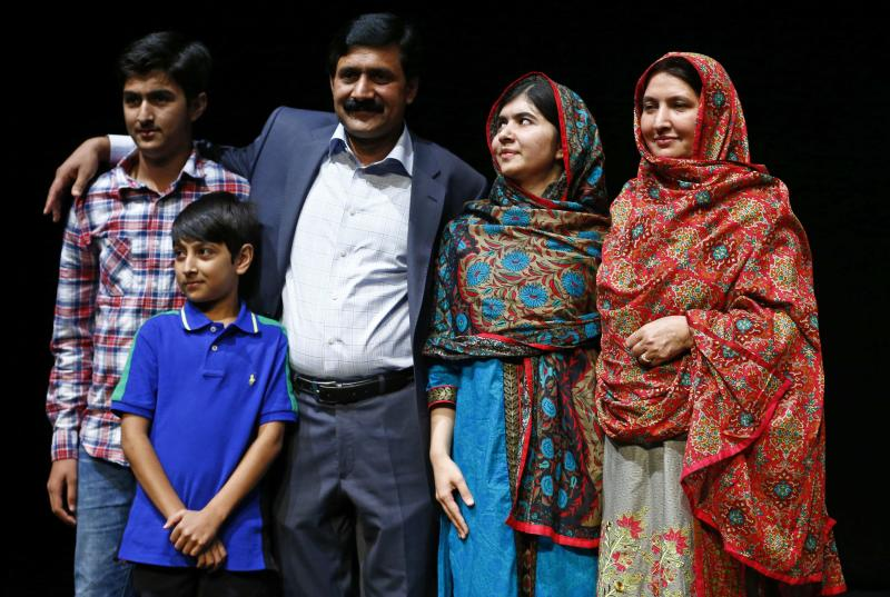 Pakistani schoolgirl Malala Yousafzai, the joint winner of the Nobel Peace Prize, stands with her family after speaking at Birmingham library in Birmingham