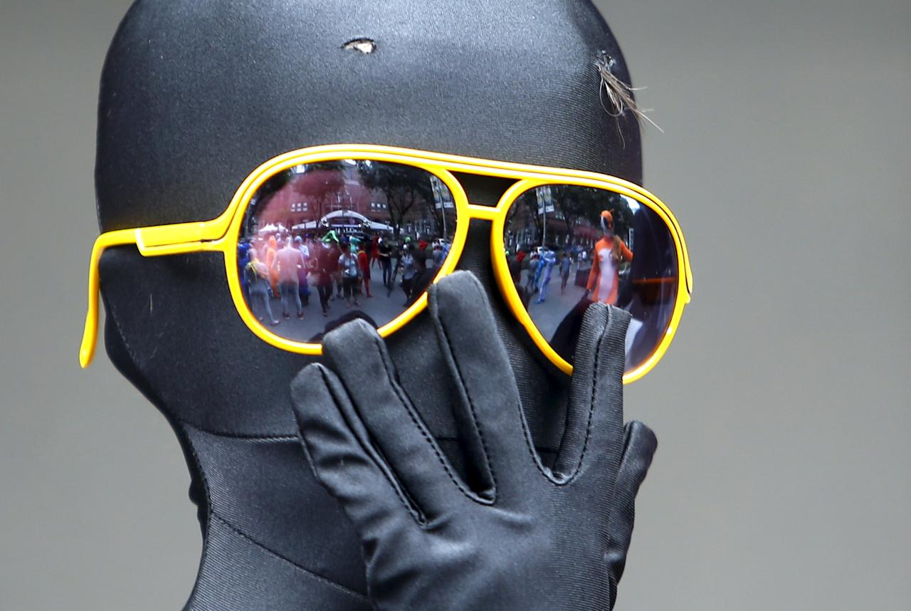 Masaru Morisako, a nine-year-old Japanese boy, looks on in his Zentai costume, or skin-tight bodysuit from head to toe, as he takes part in a march down the shopping district of Orchard Road during Zentai Art Festival in Singapore May 23, 2015. Close to 50 participants strutted down the busy shopping district during the Zentai art festival which is jointly organized by the Japanese embassy. The festival includes performances and discussions on Zentai from May 22 to from June 5. REUTERS/Edgar Su