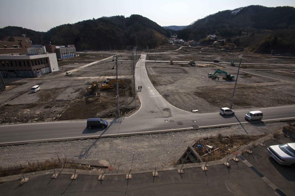 In this Feb. 22, 2012, file photo, two officials walk along a street in the tsunami and earthquake destroyed town of Onagawa, Miyagi Prefecture, northern Japan. (AP Photo/David Guttenfelder, File)