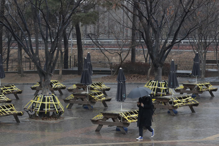 A man wearing a face mask as a precaution against the coronavirus walks past benches and tables taped for social distancing in Seoul, South Korea, Thursday, Jan. 21, 2021. (AP Photo/Lee Jin-man)