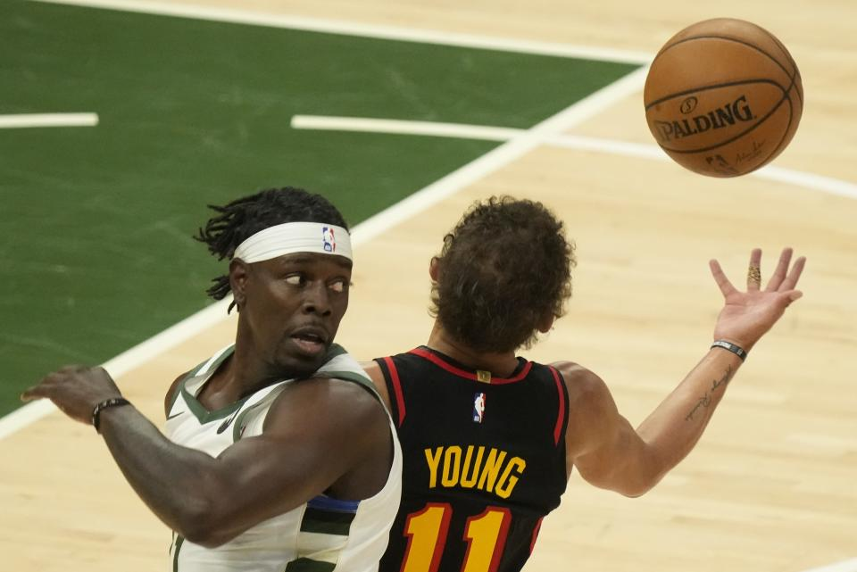 Atlanta Hawks' Trae Young steals the ball from Milwaukee Bucks' Jrue Holiday during the first half of Game 2 of the NBA Eastern Conference basketball finals game Friday, June 25, 2021, in Milwaukee. (AP Photo/Morry Gash)