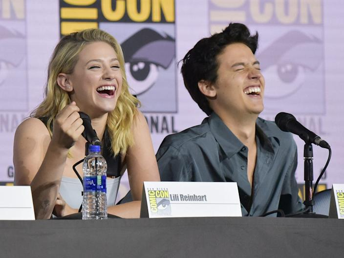 """Lili Reinhart, left, and Cole Sprouse participate in the """"Riverdalel"""" panel on day four of Comic-Con International on Sunday, July 21, 2019, in San Diego."""