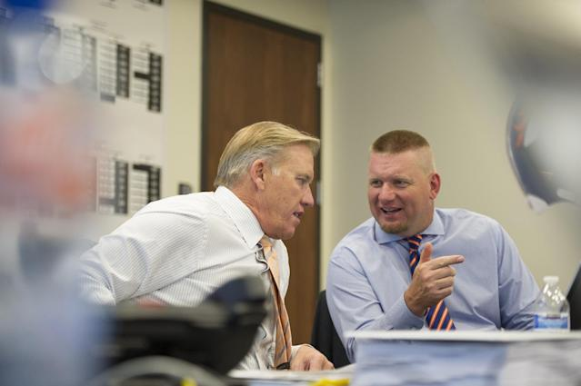 "In this photo provided by the Denver Broncos, Denver Broncos vice president John Elway, left, talks to Matt Russell, director of player personnel in the ""War Room"" during the NFL draft at the NFL football teams headquarters in Englewood, Colo., on Thursday, May 8, 2014. The Broncos are scheduled to pick 31st in the first round.(AP Photo/Denver Broncos, Eric Lars Bakke)"