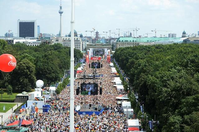 "Soccer fans and supporters of the national soccer squad gather on the so called 'Fan Mile' near the Brandenburg Gate in Berlin , Tuesday July 15, 2014. Germany's World Cup winners shared their fourth title with hundreds of thousands of fans by parading the trophy through cheering throngs to celebrate at the Brandenburg Gate on Tuesday. An estimated 400,000 people packed the ""fan mile"" in front of the Berlin landmark to welcome home coach Joachim Loew's team and the trophy which returned to Germany for the first time in 24 years. (AP Photo/dpa,Britta Pedersen)"