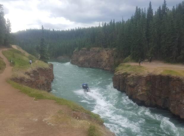 An RCMP boat travels through Miles Canyon in Whitehorse. Police said this week they've responded to nine calls so far this year involving people on waterways in Whitehorse. (Paul Tukker/CBC - image credit)