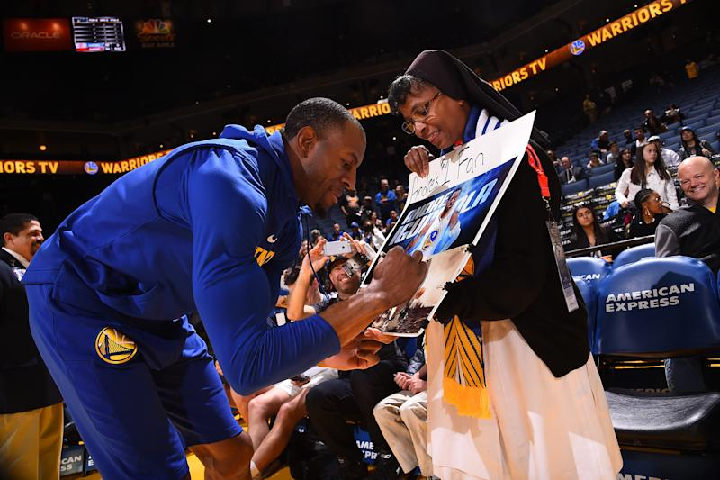 Andre Iguodala #9 of the Golden State Warriors signs an autograph for a fan before the game against the Utah Jazz on March 25, 2018 at ORACLE Arena in Oakland, California.