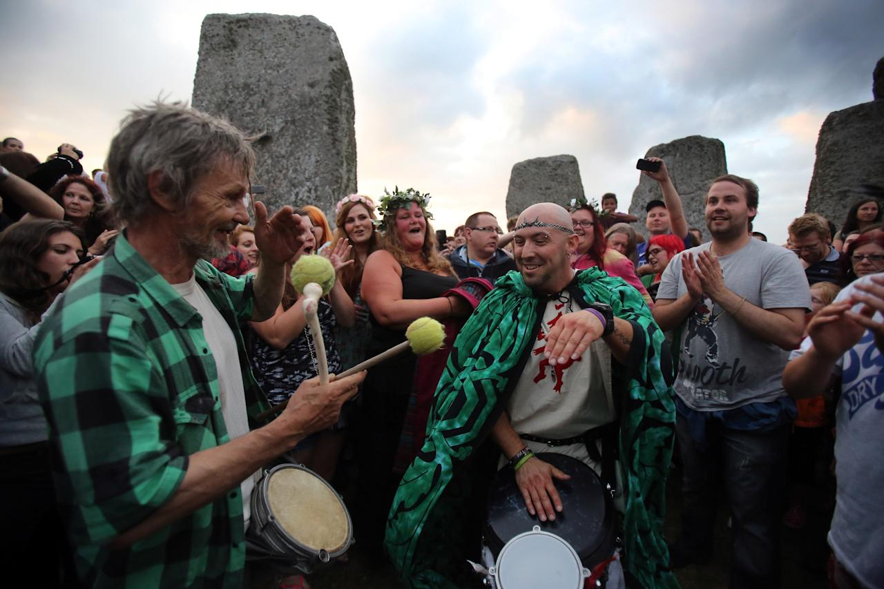Revellers dance in the centre of the stones as they wait for the arrival of the midsummer dawn at the megalithic monument of Stonehenge on June 20, 2013 near Amesbury, England. Despite cloudy skies, thousands of revellers gathered at the 5,000 year old stone circle in Wiltshire to see the sunrise on the Summer Solstice dawn. The solstice sunrise marks the longest day of the year in the Northern Hemisphere. (Photo by Matt Cardy/Getty Images)