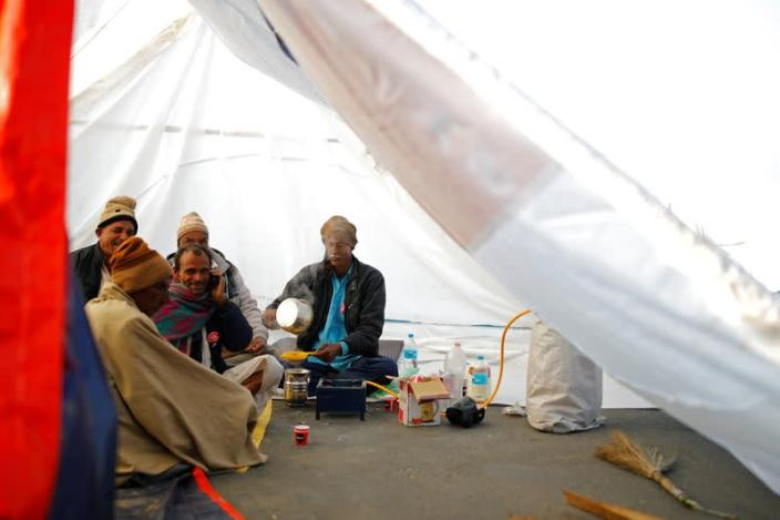 Farmers make tea inside a tent at the site of a protest against new farm laws, at a state border on a national highway, in Shahjahanpur