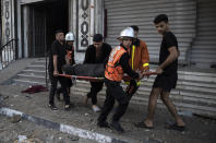 Palestinian rescuers evacuate an elderly woman from a building following Israeli airstrikes on Gaza City, Wednesday, May 12, 2021. Rockets streamed out of Gaza and Israel pounded the territory with airstrikes early Wednesday as the most severe outbreak of violence since the 2014 war took on many of the hallmarks of that devastating 50-day conflict, with no endgame in sight. (AP Photo/Khalil Hamra)