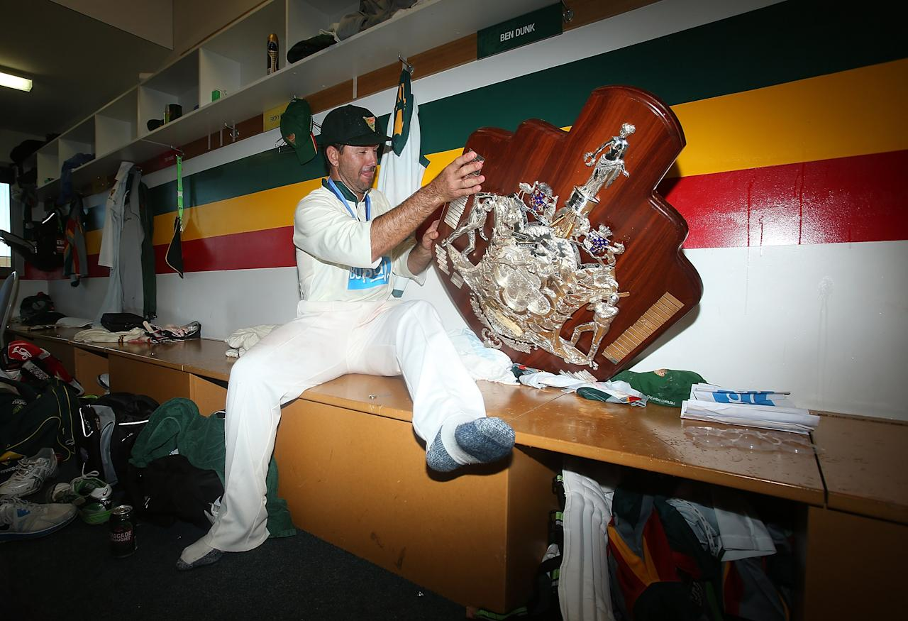 HOBART, AUSTRALIA - MARCH 26:  Ricky Ponting of the Tigers struggles to stop the Sheffield Shield trophy toppling over in the changing rooms after winning the Sheffield Shield final between the Tasmania Tigers and the Queensland Bulls at Blundstone Arena on March 26, 2013 in Hobart, Australia.  (Photo by Mark Metcalfe/Getty Images)