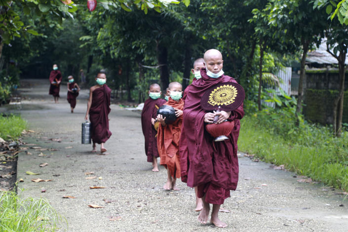 Buddhist monks wearing face mask walk as they collect morning alms Thursday, July 15, 2021, in Yangon, Myanmar. (AP Photo/Thein Zaw)