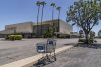 This Thursday, May 27, 2021, photo shows an empty shopping cart in an empty parking lot at the closed Sears in Buena Park Mall in Buena Park, Calif. California state lawmakers are grappling with a particularly 21st-century problem: What to do with the growing number of shopping malls and big-box retail stores left empty by consumers shifting their purchases to the web. A possible answer in crowded California cities is to build housing on these sites, which already have ample parking and are close to existing neighborhoods. Even before the pandemic, big-box retail stores struggled to adapt as more people began buying things online. In 2019, after purchasing Sears and Kmart, Transformco closed 96 stores across the country, 29 in California. (AP Photo/Damian Dovarganes)