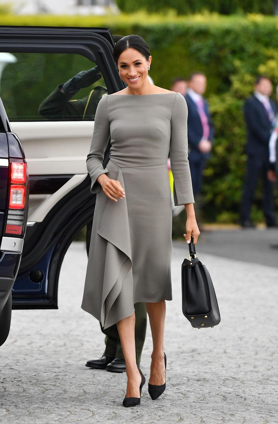 <p>To visit Irish President Michael Higgins and his wife, Sabina, at their residence, Áras an Uachtaráin, Meghan wore a bespoke earth-toned Roland Mouret dress, not dissimilar to the navy dress Meghan wore by the same designer the night before her wedding. <br><em>[Photo: PA]</em> </p>