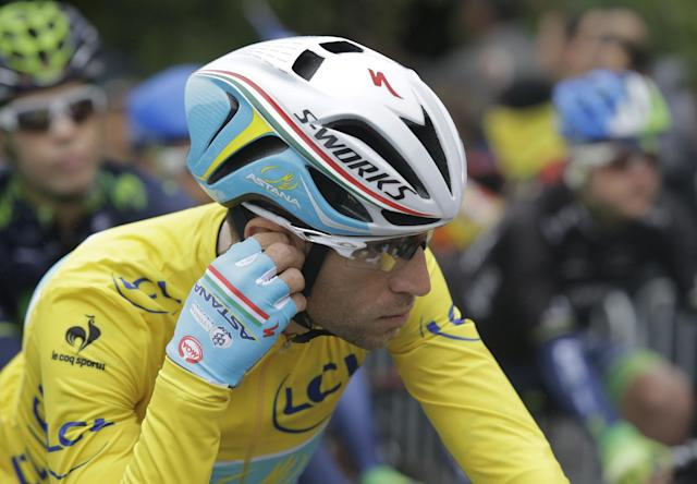 Italy's Vincenzo Nibali, wearing the overall leader's yellow jersey, adjusts his earpiece during the sixth stage of the Tour de France cycling race over 194 kilometers (120.5 miles) with start in Arras and finish in Reims, France, Thursday, July 10, 2014. (AP Photo/Laurent Cipriani)