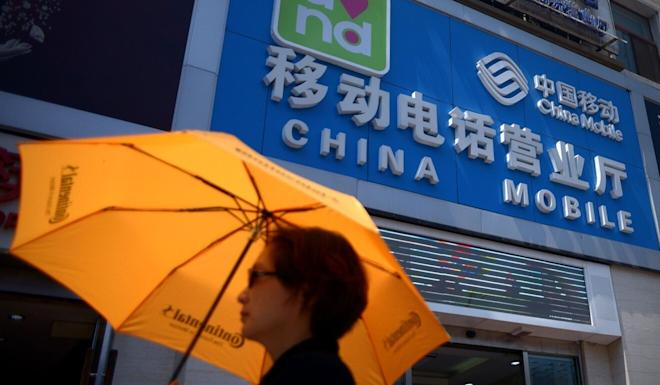 A woman walks past a China Mobile store in Beijing in August 2014. Photo: AFP