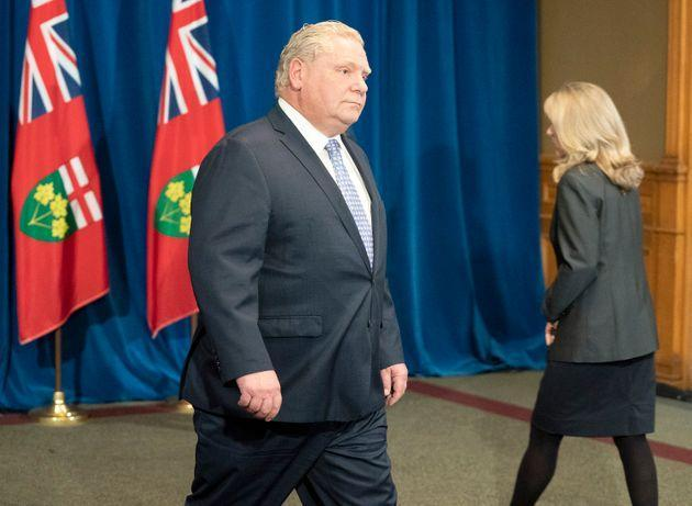 Ontario Premier Doug Ford passes Minister of Long-Term Care Merrilee Fullerton during the government's daily briefing at Queen's Park in Toronto on May 28, 2020.