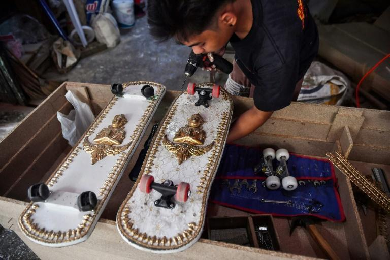 An employee from the Burapha coffin shop in Bangkok putting wheels on skateboards, made from wood used for coffins
