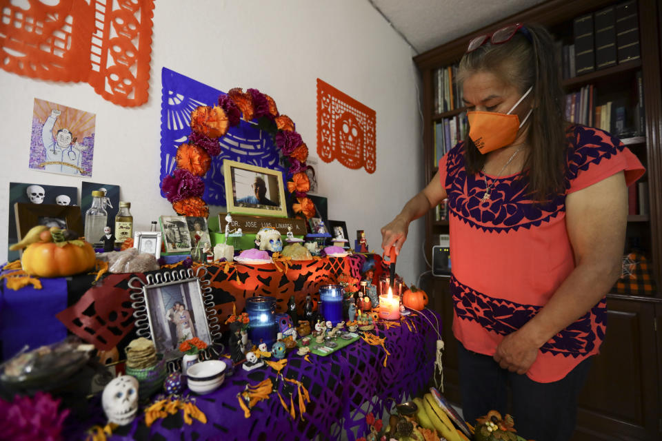 Rosario Martinez, lights candles on a Day of the Dead altar for her husband Dr. Jose Luis Linares, who died from symptoms related to COVID-19, at their home in Mexico City, Sunday, Nov. 1, 2020. He is one of more than 1,700 Mexican health workers officially known to have died of COVID-19 who are behind honored with three days of national mourning on these Days of the Dead. (AP Photo/Eduardo Verdugo)