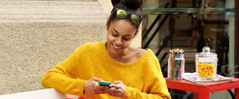 Portrait of relaxed young woman sitting outdoor on bench with shopping bags and using mobile phone