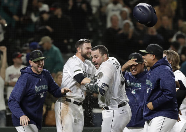 Seattle Mariners Mike Zunino, third from left, celebrates with teammates after he hit a walk-off solo home run against the Minnesota Twins during the 12th inning of a baseball game, Saturday, May 26, 2018, in Seattle. The Mariners won 4-3. (AP Photo/Ted S. Warren)
