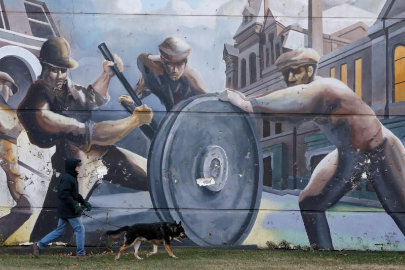 A man walks his dog past a mural depicting factory workers in Chicago's historic Pullman neighborhood.
