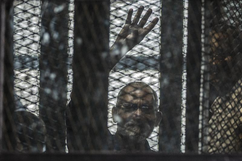 Egyptian Muslim Brotherhood leader Mohamed Badie gestures from inside the defendants cage during his trial along with other senior members of the group at the Tura prison police institute on the outskirts of Cairo on August 3, 2014