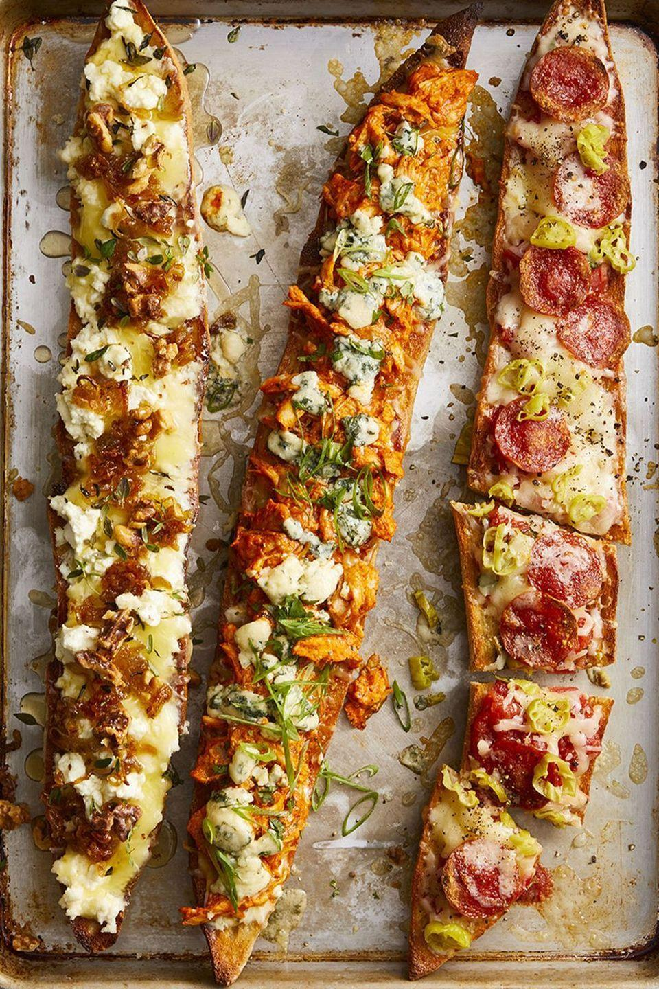 """<p>Is no game day in your household complete without a pizza or two. Give your guests an elevated version with these baked baguettes, featuring ingredients like Buffalo chicken, shallots and goat cheese, and pepperoni.</p><p><em><a href=""""https://www.goodhousekeeping.com/food-recipes/easy/a47670/baguette-pizza-recipe/"""" rel=""""nofollow noopener"""" target=""""_blank"""" data-ylk=""""slk:Get the recipe for Baguette Pizza»"""" class=""""link rapid-noclick-resp"""">Get the recipe for Baguette Pizza»</a></em></p>"""