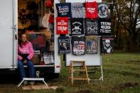 A vendor sells merchandise to supporters of U.S. President Trump as they wait in line to attend his campaign event in Erie