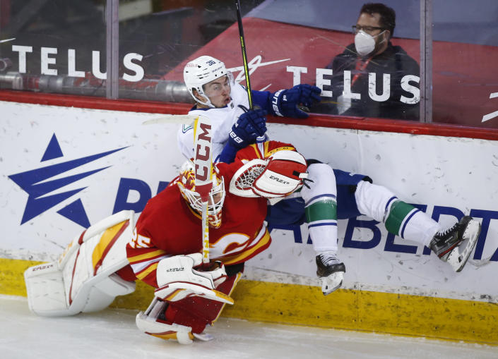 Vancouver Canucks' Nils Hoglander, right, is checked by Calgary Flames goalie Jacob Markstrom during the third period of an NHL hockey game Thursday, May 13, 2021, in Calgary, Alberta. (Jeff McIntosh/The Canadian Press via AP)