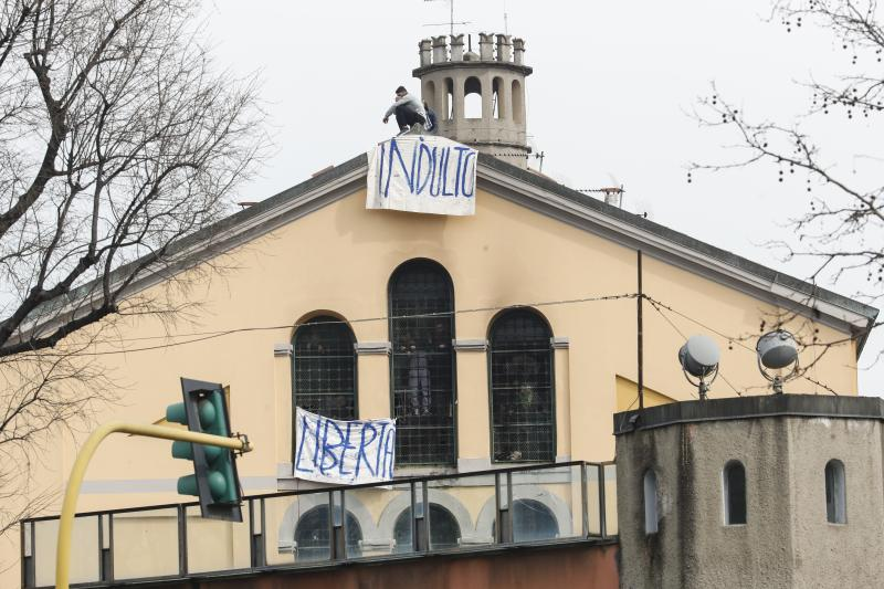 Pictured is two white banners erected on the facade of the prison in Milan.