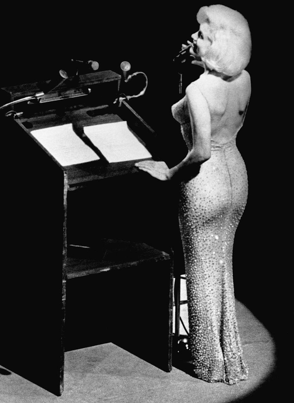 """<p>Marilyn serenaded John F. Kennedy for his 45th birthday with her now-iconic rendition of """"Happy Birthday."""" She was sewn into her stunning, shimmering gown adorned with more than 2,500 rhinestones.</p>"""
