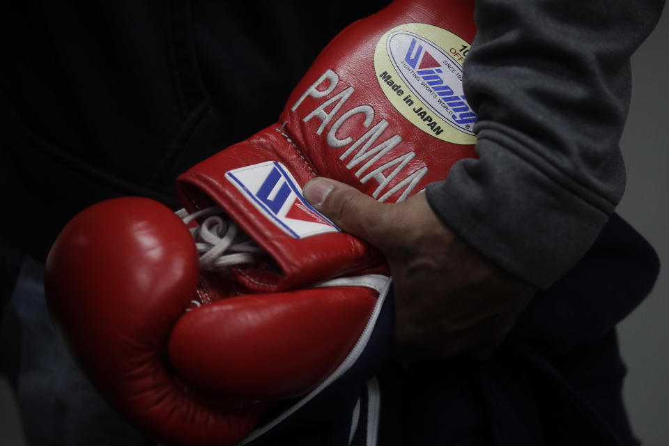A trainer holds boxer Manny Pacquiao's gloves with Pacquiao's nickname embroidered on them at the Wild Card Boxing Club Monday, Jan. 14, 2019, in Los Angeles. The Filipino legend is in the winter of his career, gearing up for what could be one big last fight. Saturday's bout versus Broner isn't it, but Pacquiao trains with the knowledge that a second megafight against Floyd Mayweather could possibly be just months away if all goes well. (AP Photo/Jae C. Hong)