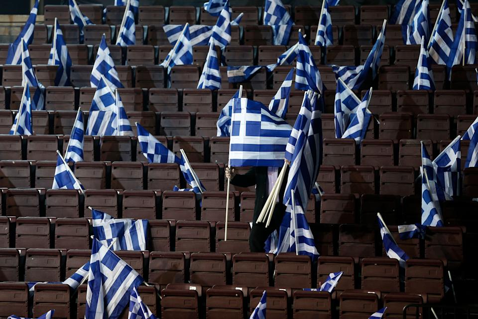 A man places Greek flags on seats for New Democracy party supporters ahead of Prime Minister's Antonis Samaras pre-election speech at the Taekwondo Indoor Stadium in southern Athens on Friday, Jan. 23, 2015. (AP Photo/Petros Giannakouris)