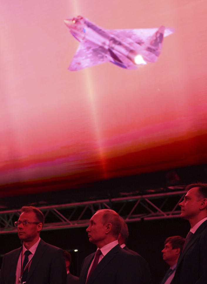 Russian President Vladimir Putin, center, inspects a prototype of a new fighter jet that features stealth capabilities and other advanced characteristics at the MAKS-2021 International Aviation and Space Salon outside Zhukovsky, Russia, Tuesday, July 20, 2021. (Alexei Nikolsky, Sputnik, Kremlin Pool Photo via AP)