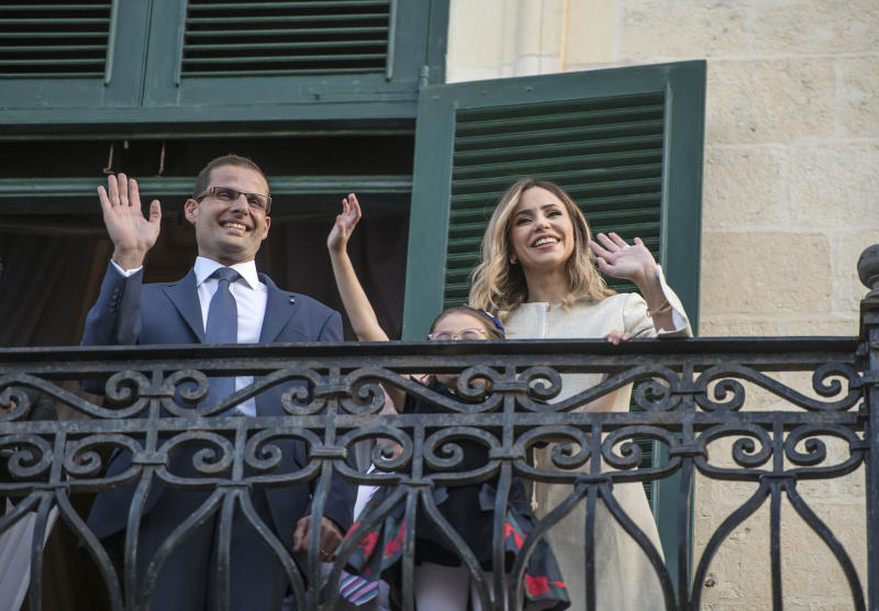 The new Prime Minister of Malta Robert Abela waves to the crowd from the President of Malta's balcony after the swearing in ceremony, together with his wife Lydia Abela and his daughter Giorgia Mae, Monday, Jan. 13, 2020. Abela is replacing Joseph Muscat after weeks of protests demanding accountability in the investigation of the car bomb slaying of an anti-corruption journalist who targeted his government. (AP Photo/Rene' Rossignaud)