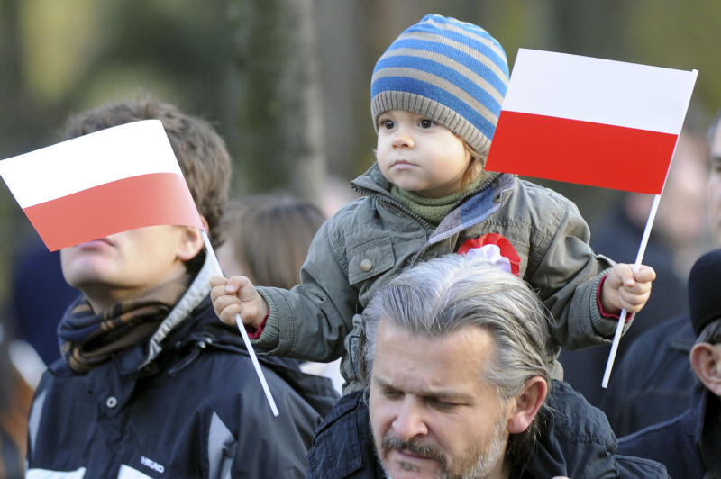 A small boy holds Polish national flags, during a ceremony marking Independence Day, in Warsaw, Poland, Sunday, Nov. 11, 2012. (AP Photo/Alik Keplicz)