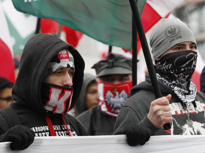 Masked members of radical right-wing groups wave flags during a march by tens of thousands of people and hosted by President Andrzej Duda that marked 100 years since Poland regained independence in Warsaw, Poland, Sunday, Nov. 11, 2018. (AP Photo/Czarek Sokolowski)