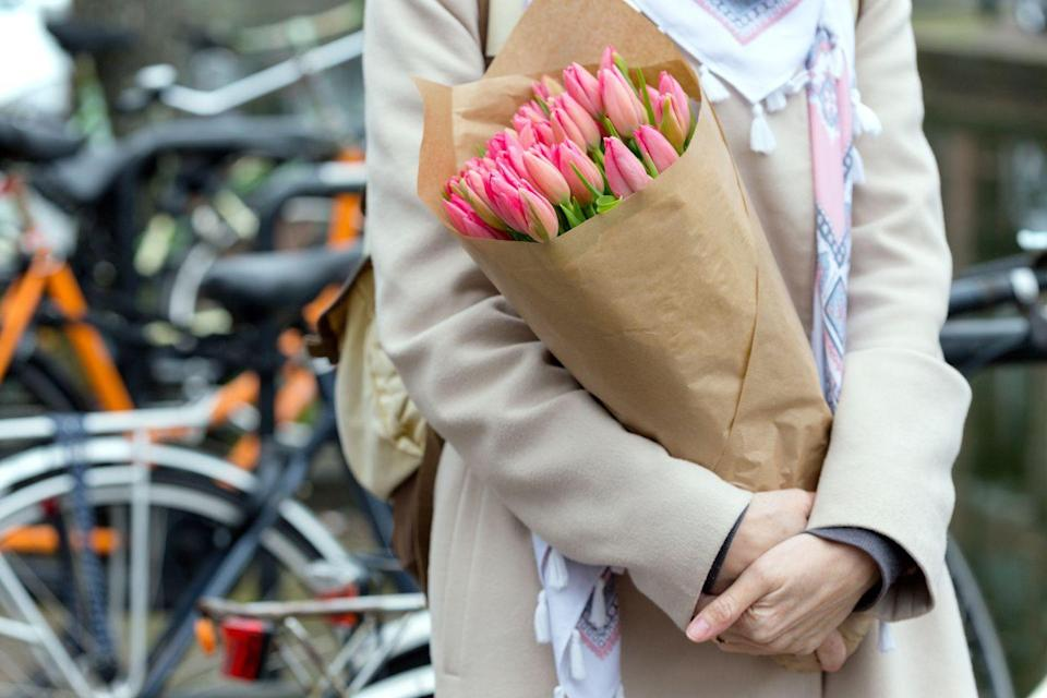 <p>A woman holding a bouquet of tulips in Amsterdam </p>